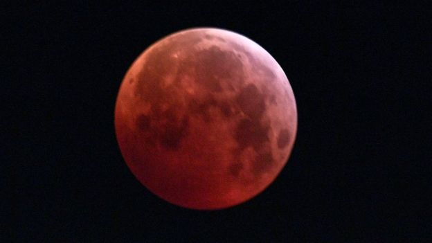 The so-called Super Blood Wolf Moon is engulfed into Earth's dark umbral shadow during a total lunar eclipse over Milan, north Italy on January 21, 2019